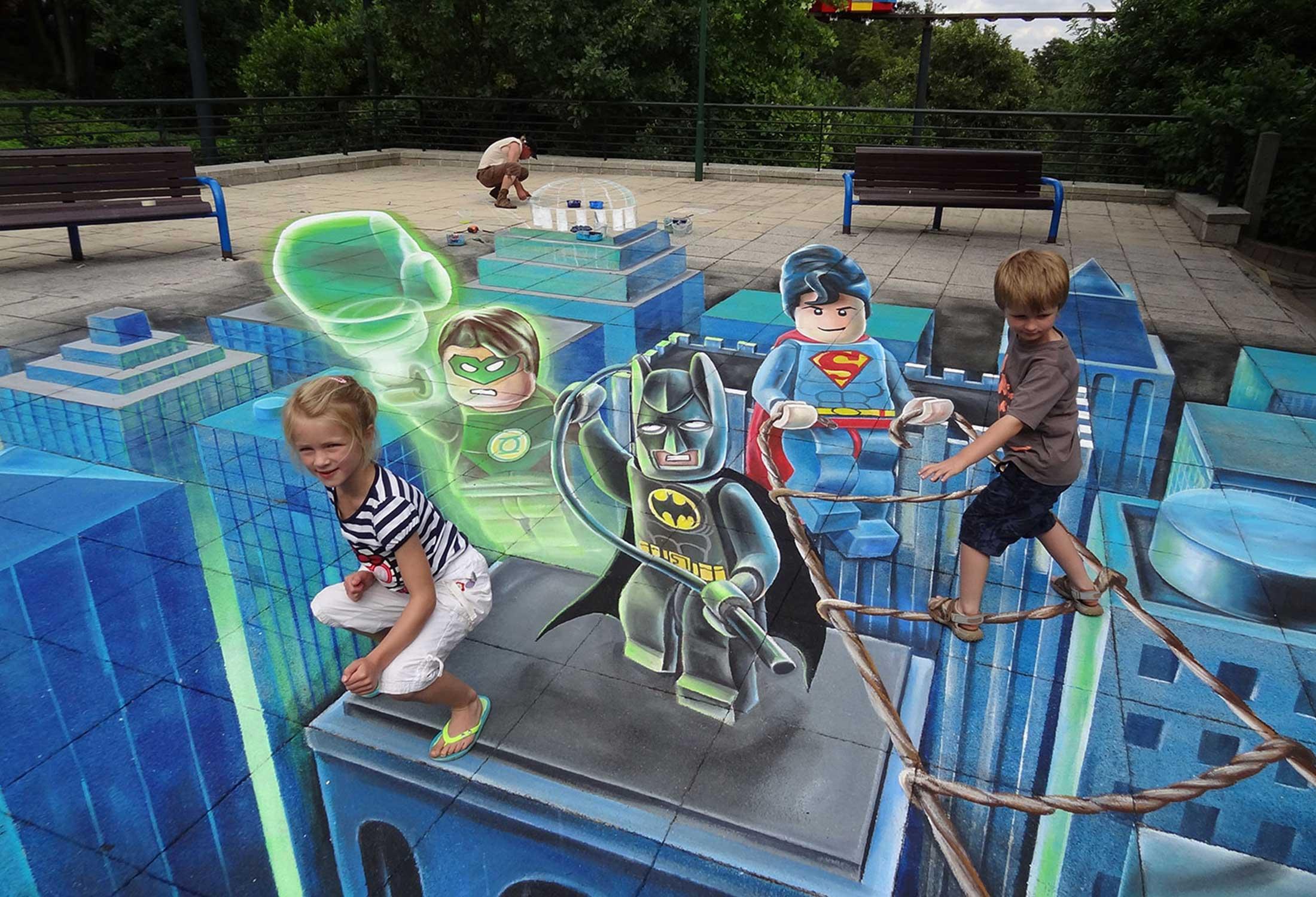 3D urban art by Leon Keer featuring Lego Batman, Lego Superman, and Lego Green Lantern