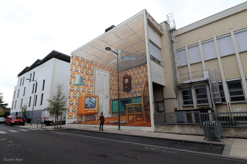 A viewer of the Once Upon a Time mural stands closely to analyze the illusionistic mura